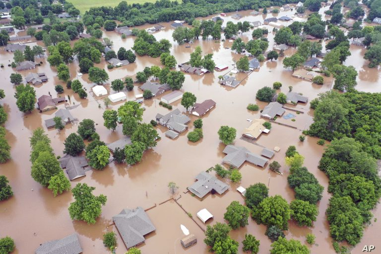This Tuesday, May 28, 2019, aerial photo shows flooded homes along the Arkansas River in Sand Spring, Okla. Communities that have seen little rain are getting hit by historic flooding along the Arkansas River thanks to downpours upstream that have prompted officials to open dams to protect some cities but inundate others with swells of water. (DroneBase via AP)